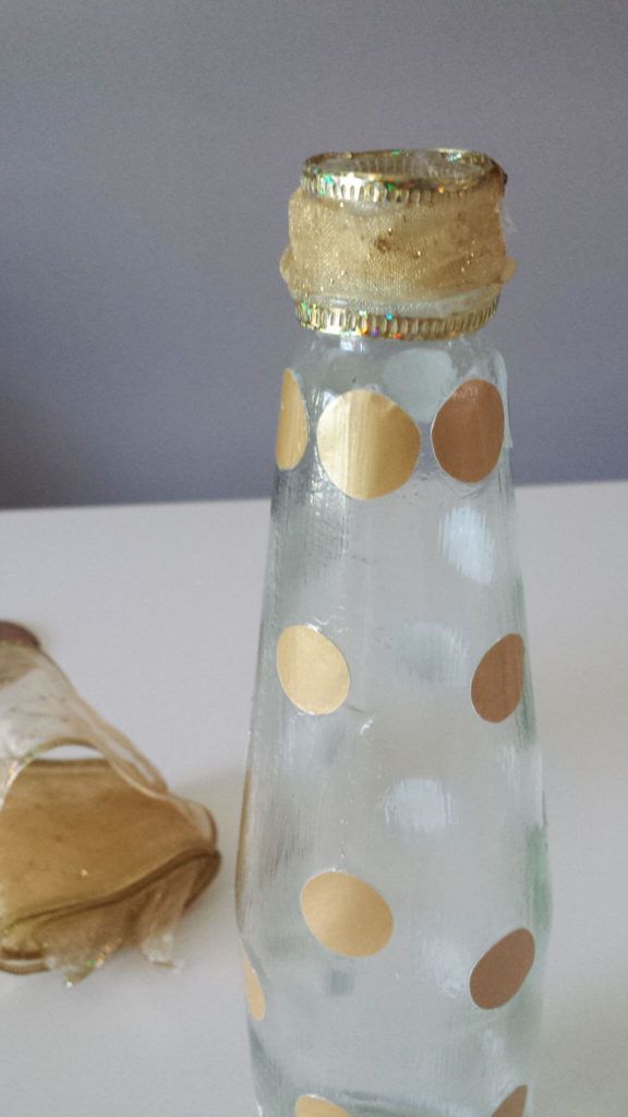 gold ribbon on repurposed sauce bottle